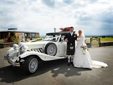 Bride and Groom beside Beauford Limousine