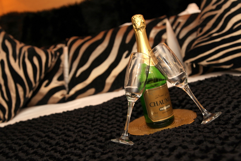 Champagne Glasses and Champagne on Bed